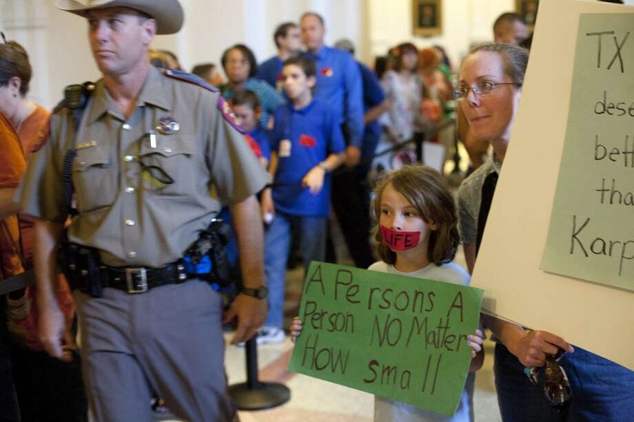 Linda Maska and Theresa Maska, 8, hold anti-abortion rights signs outside of the Senate Gallery in the State Capitol in Austin, Texas on Friday, July 12, 2013. The Texas Senate's leader, Lt. Gov. David Dewhurst, has scheduled a vote for Friday on the same restrictions on when, where and how women may obtain abortions in Texas that failed to become law after a Democratic filibuster and raucous protesters were able to run out the clock on an earlier special session. (AP Photo/Tamir Kalifa) Photo: AP