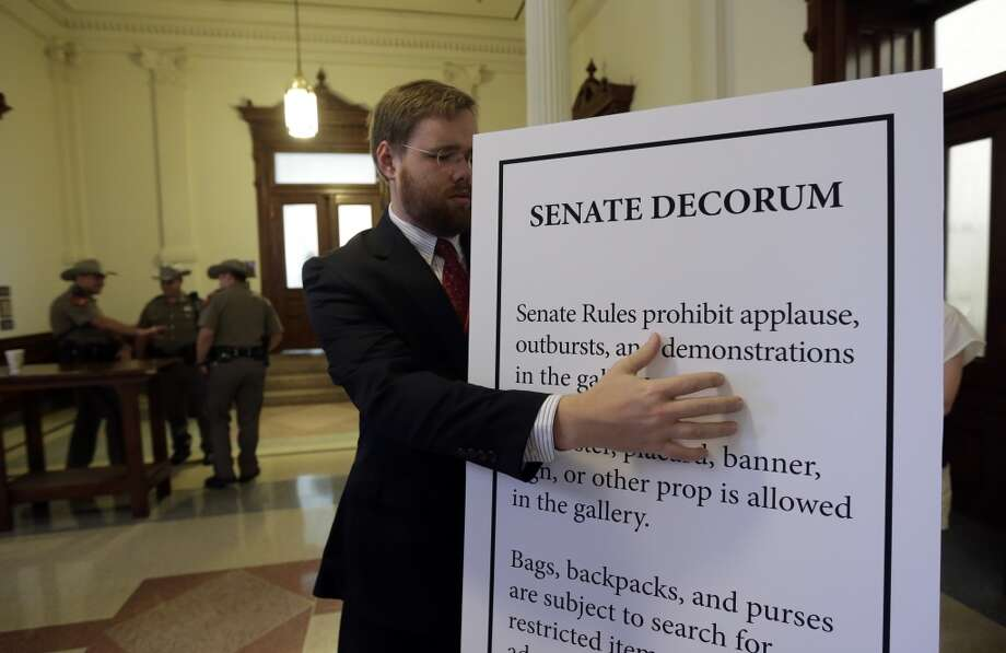 Assistant sergeant of arms Will Wassdorf sets up a display with rules for the gallery outside the Texas Senate chambers as he final vote by the Senate is expected to begin, Friday, July 12, 2013, in Austin, Texas. The bill would require doctors to have admitting privileges at nearby hospitals, only allow abortions in surgical centers, dictate when abortion pills are taken and ban abortions after 20 weeks. (AP Photo/Eric Gay) Photo: AP
