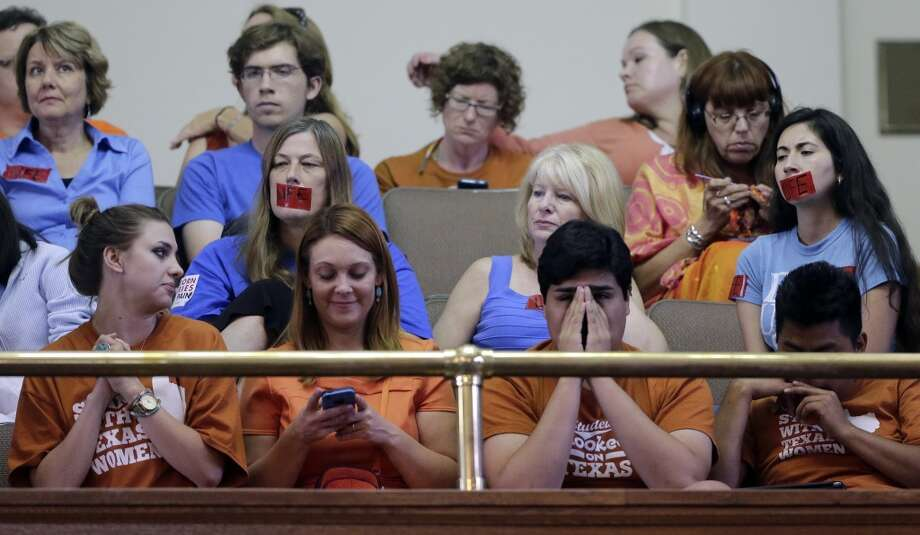 Supporters and opponents of an abortion bill, mostly dressed in blue or orange to show their side, sit in the gallery of the Texas Senate chambers as lawmakers debate before the final vote, Friday, July 12, 2013, in Austin, Texas. The bill would require doctors to have admitting privileges at nearby hospitals, only allow abortions in surgical centers, dictate when abortion pills are taken and ban abortions after 20 weeks. (AP Photo/Eric Gay) Photo: AP