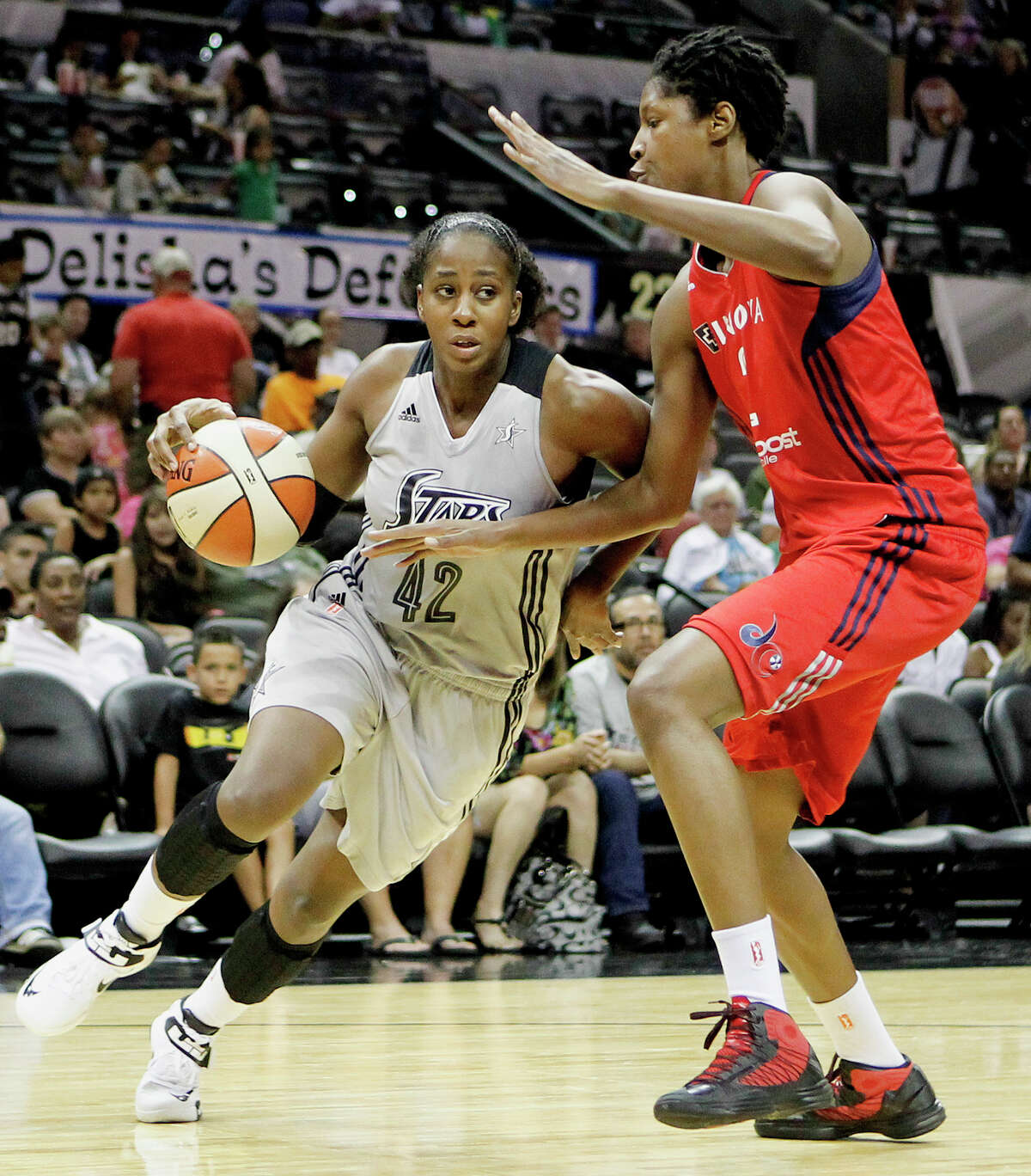 Shenise Johnson of the Silver Stars (left) drives around Michelle Snow of the Washington Mystics during the third quarter of their game at the AT&T Center on Friday, July 12, 2013. The Mystics downed the Silver Stars 83-73. MARVIN PFEIFFER/ mpfeiffer@express-news.net