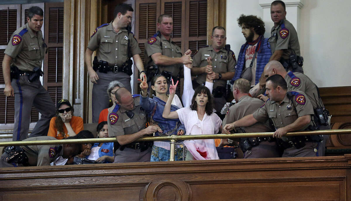 DPS troopers arrest protesters who chained themselves to a railing in the gallery.