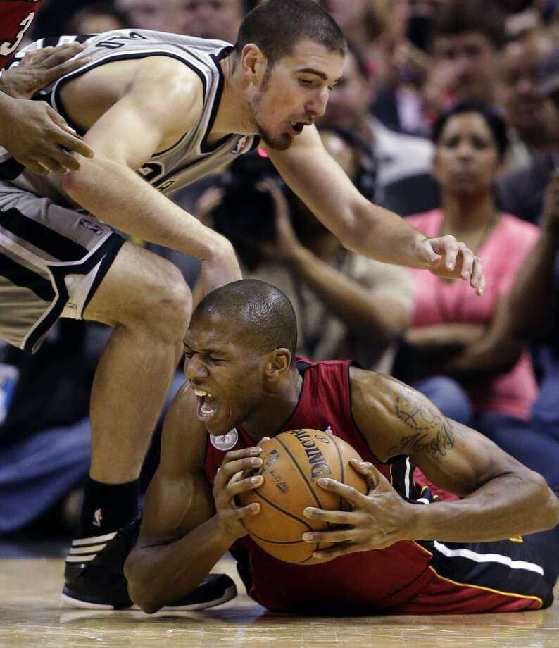 Miami Heat's James Jones, right, battles for control of a loose ball as San Antonio Spurs' Nando De Colo, left, of France, moves in during the second half of an NBA basketball game, Sunday, March 31, 2013, in San Antonio. Miami won 88-86. Photo: Eric Gay, Associated Press