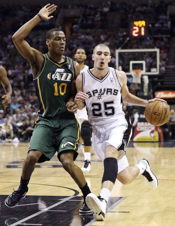 San Antonio Spurs' Nando De Colo looks for room around Utah Jazz's Alec Burks during second half action Friday March 22, 2013 at the AT&T Center. The Spurs won 104-97 in overtime. Photo: Edward A. Ornelas, San Antonio Express-News