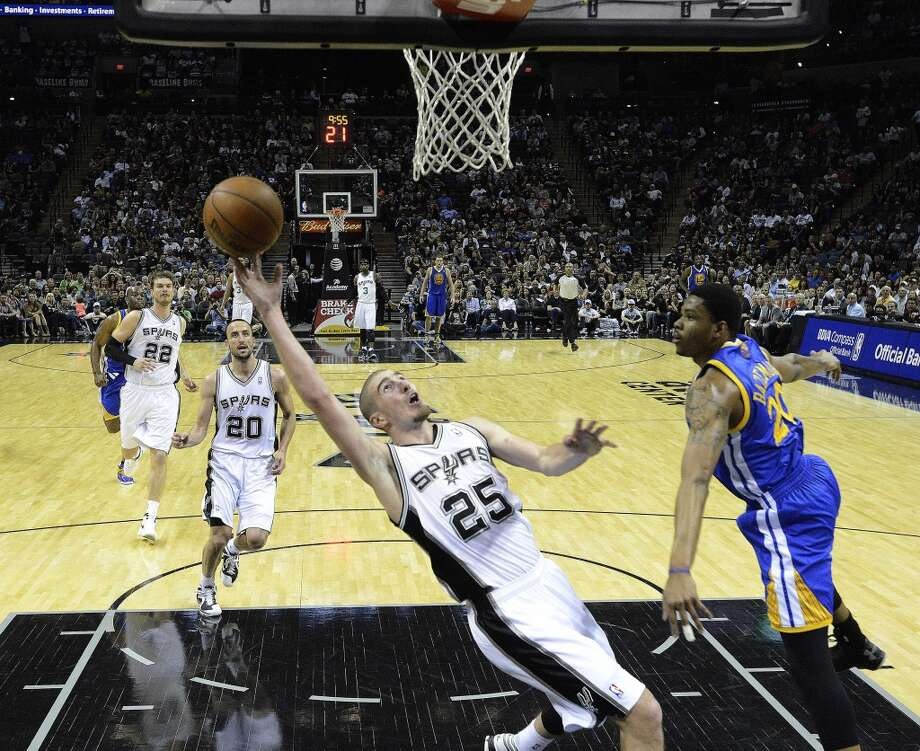 San Antonio Spurs guard Nando de Colo scores on a breakaway layup as Kent Bazemore of Golden State defends during second-half NBA action at the AT&T Center on Wednesday, March 20, 2013. The Spurs won, 104-93. Photo: Billy Calzada, San Antonio Express-News