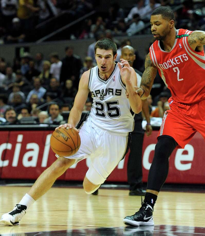 Nando De Colo of the Spurs (25) drives past Marcus Morris of the Houston Rockets in NBA action at the AT&T Center on Friday, Dec. 7, 2012. Photo: Billy Calzada, San Antonio Express-News / SAN ANTONIO EXPRESS-NEWS
