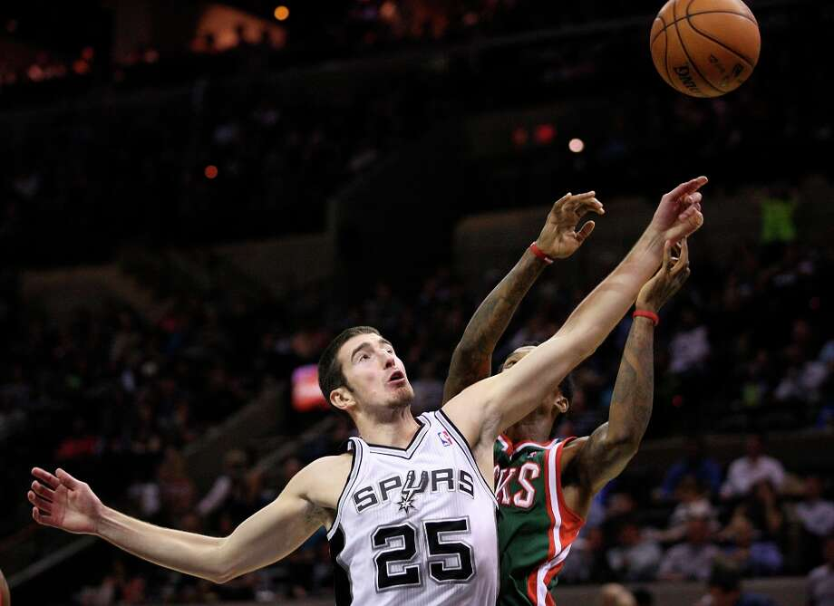 The Spurs' Nando De Colo reaches for a pass under pressure from Milwaukee Bucks' Brandon Jennings during the second half at the AT&T Center, Wednesday, Nov. 5, 2012. The Spurs won 110-99. Photo: Jerry Lara, San Antonio Express-News / © 2012 San Antonio Express-News