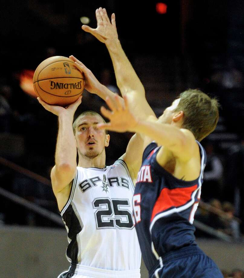 Nando de Colo of the Spurs shoots over Kyle Korver of Atlanta during first-half preseason action at the AT&T Center on Wednesday, Oct. 10, 2012. Photo: Billy Calzada, San Antonio Express-News / © San Antonio Express-News