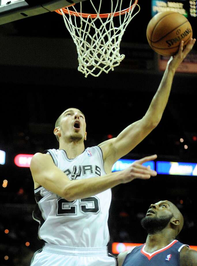Rookie Nando De Colo of the Spurs shoots a reverse layup as Ivan Johnson of Atlanta watches during preseason action at the AT&T Center on Wednesday, Oct. 10, 2012. Photo: Billy Calzada, San Antonio Express-News / © San Antonio Express-News