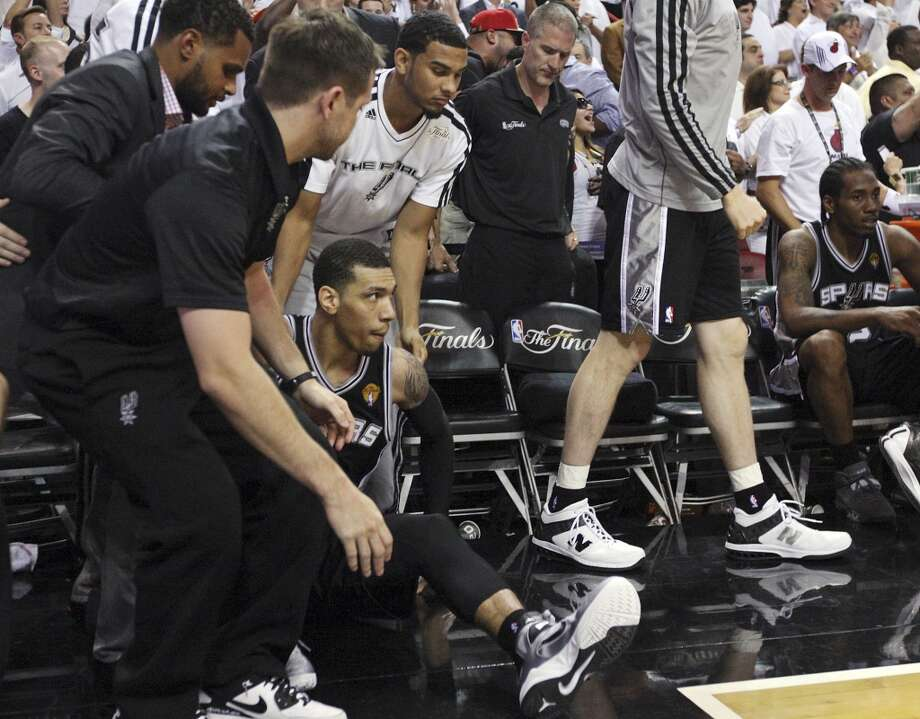 San Antonio Spurs' Danny Green is helped up by San Antonio Spurs' Patty Mills and San Antonio Spurs' Cory Joseph after missing the final shot during overtime action in Game 6 of the 2013 NBA Finals Tuesday, June 18, 2013 at American Airlines Arena in Miami. The Heat won 103-100.