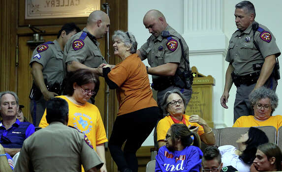 A protestor is removed as the Senate debates passage of abortion legislation on July 12, 2013. Photo: Tom Reel, San Antonio Express-News