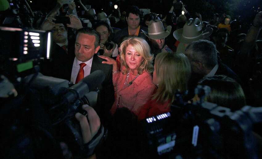 Wendy Davis leans on Carlos Uresti as they exit a rally in front of the Capitol after the Senate passes abortion legislation on July 12, 2013.