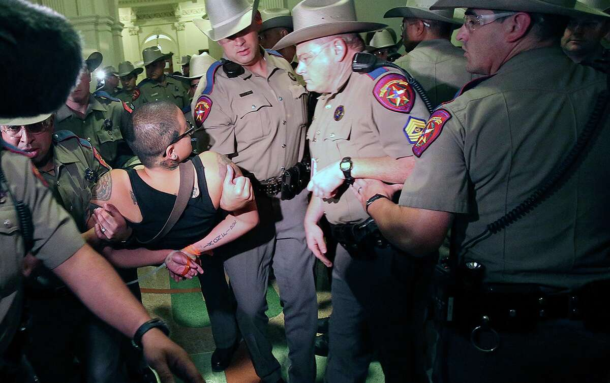 A protestor is hauled away by DPS officers after the Senate passes abortion legislation on July 12, 2013.