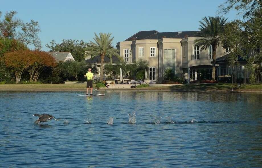 A goose takes off the other direction from a stand-up paddle boarder on Bayou St. John.