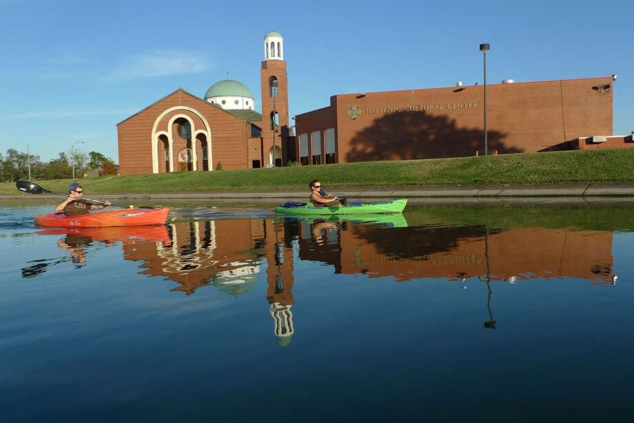 Kayakers ride through the glassy reflection of the Holy Trinity Cathedral in New Orleans.
