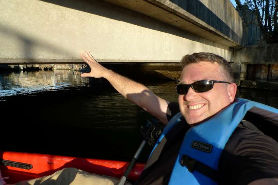 Chronicle Travel Editor Spud Hilton demonstrates the how low the final two bridges are over Bayou St. John.