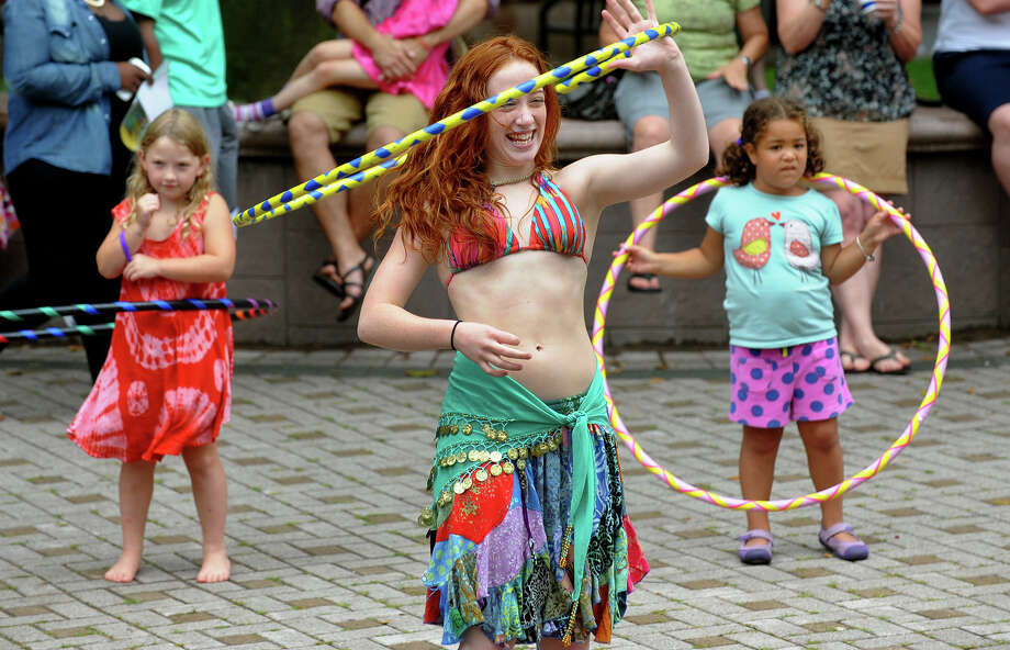 Courtney Kapral, of Shelton, with the club Bring the Hoopla, has fun hula hooping while the band Alpaca Gnomes perform, during the 4th Annual Bridgeport Arts Festival on McLevy Green in downtown Bridgeport, Conn. on Saturday July 13, 2013. In back also hula hooping are Lily Curtin, 6, at left, and Lila Fabian, 6, both from Bridgeport. Photo: Christian Abraham / Connecticut Post