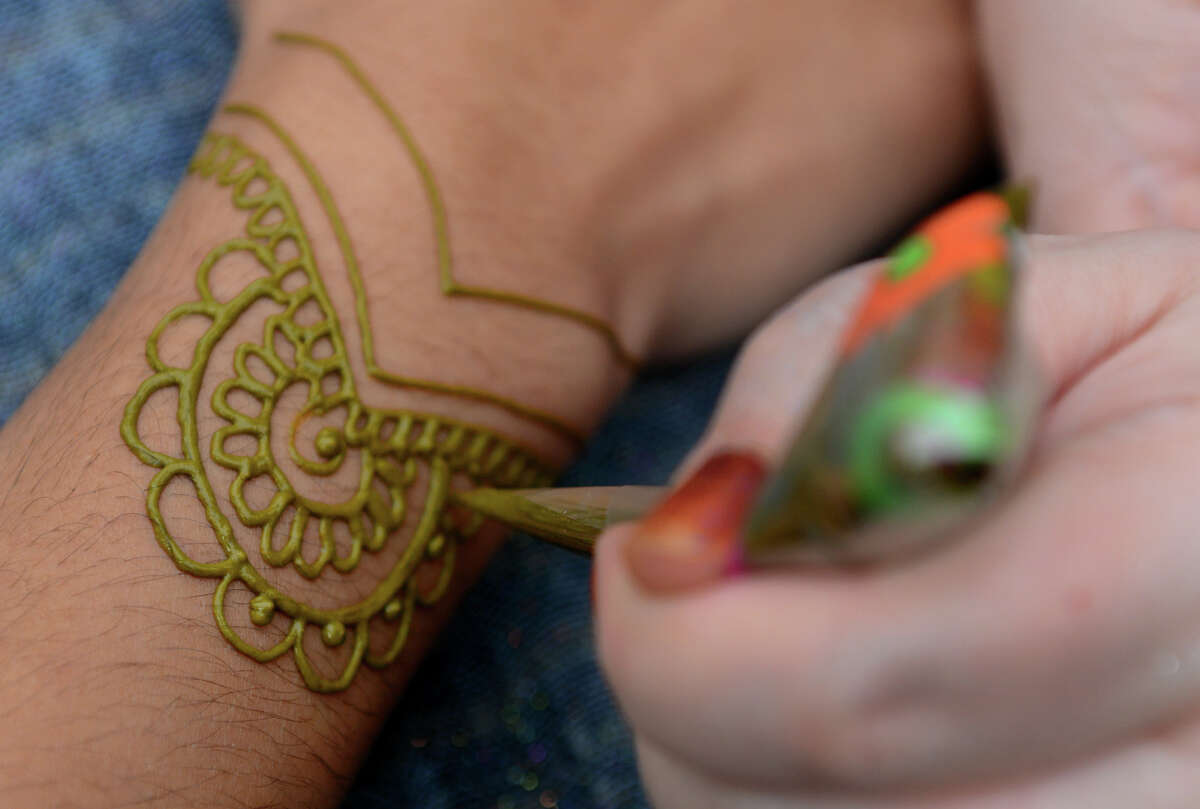 Jamilah Zebarth, who operates Jamilah Henna Creations, creates a henna tattoo for a customer, during the 4th Annual Bridgeport Arts Festival on McLevy Green in downtown Bridgeport, Conn. on Saturday July 13, 2013.
