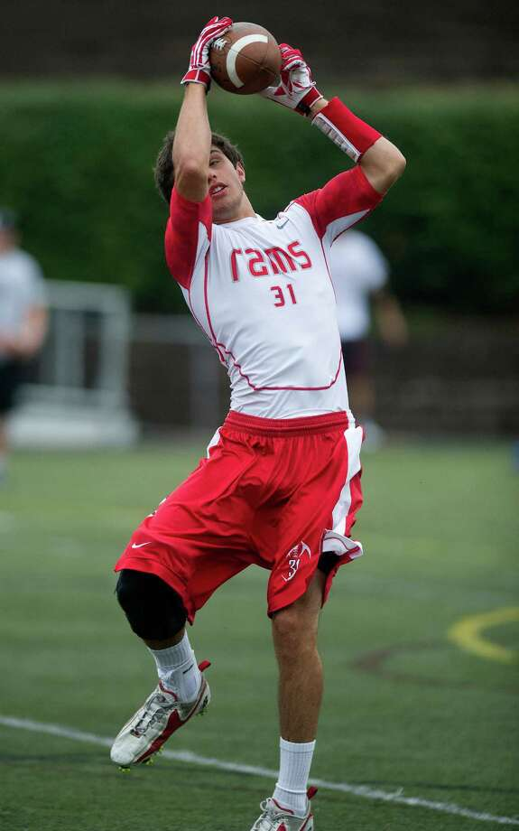 "New Canaan's Mike DiCosmo makes a catch during Saturday's ""Grip It and Rip It"" high school football passing camp and competition at New Canaan High School on July 13, 2013. Photo: Lindsay Perry / Stamford Advocate"