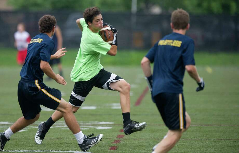 "New Milford's Trevor Hallas carries the ball during Saturday's ""Grip It and Rip It"" high school football passing camp and competition at New Canaan High School on July 13, 2013. Photo: Lindsay Perry / Stamford Advocate"