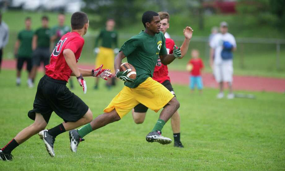 """Trinity Catholic's Neno Merritt carries the ball during Saturday's """"Grip It and Rip It"""" high school football passing camp and competition at New Canaan High School on July 13, 2013. Photo: Lindsay Perry / Stamford Advocate"""