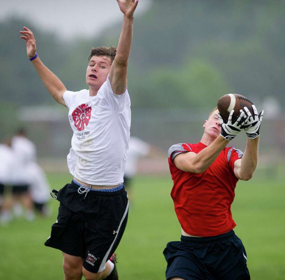 "Fairfield Prep's Jake Buckley, left, and Greenwich's Devin McGrath, right, play in Saturday's ""Grip It and Rip It"" high school football passing camp and competition at New Canaan High School on July 13, 2013. Photo: Lindsay Perry / Stamford Advocate"