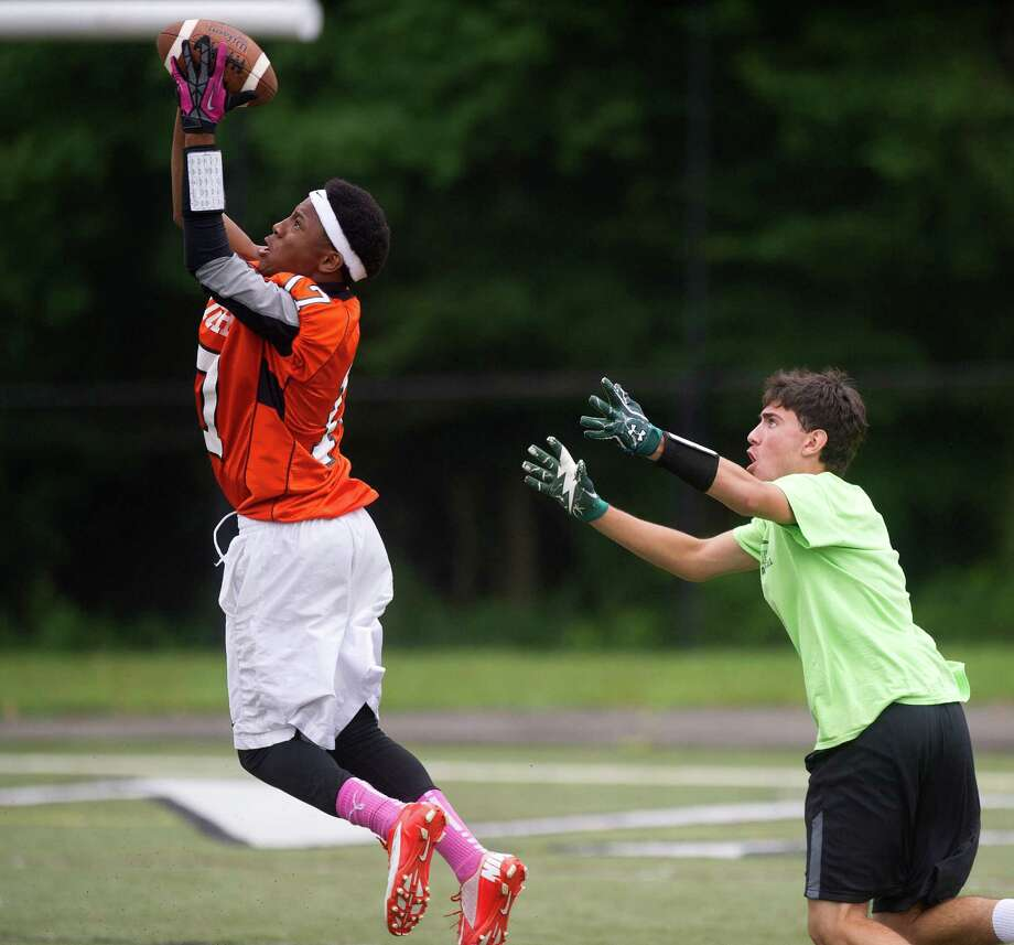 "Patrick Dircile of Stamford jumps to make a catch as New Milford's Grant Murphy looks on during Saturday's ""Grip It and Rip It"" high school football passing camp and competition at New Canaan High School on July 13, 2013. Photo: Lindsay Perry / Stamford Advocate"