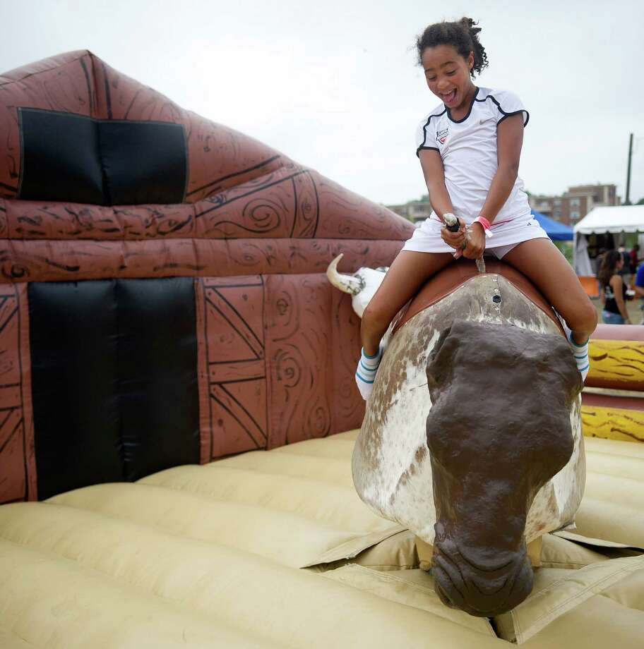 Audrey Magnusen rides the mechanical bull during Pork in the Park at Mill River Park on Saturday, July 13, 2013. Photo: Lindsay Perry / Stamford Advocate