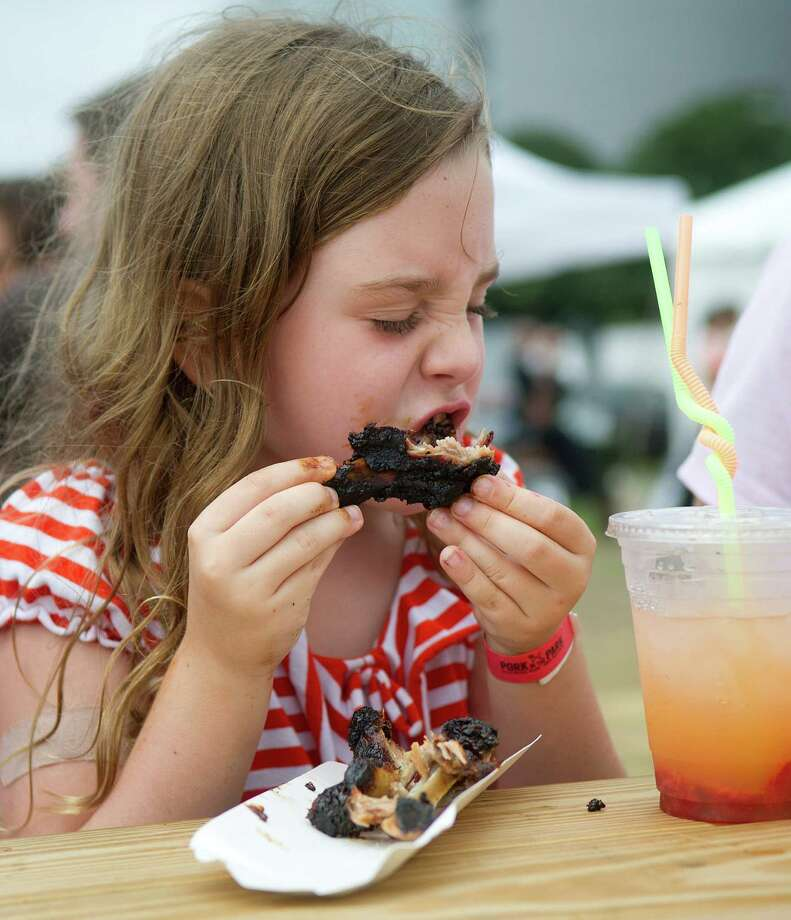 Alexandra Gelvin eats ribs during Pork in the Park at Mill River Park on Saturday, July 13, 2013. Photo: Lindsay Perry / Stamford Advocate