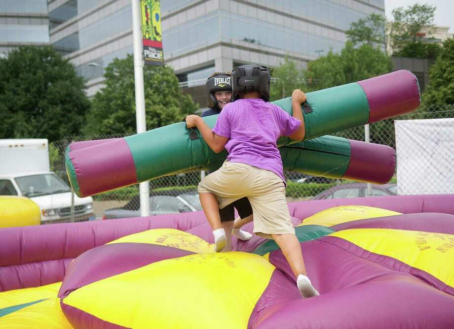 Zachary Frattaroli, back, and Eddye Ramirez, 7, play on an inflatable during Pork in the Park at Mill River Park on Saturday, July 13, 2013. Photo: Lindsay Perry / Stamford Advocate