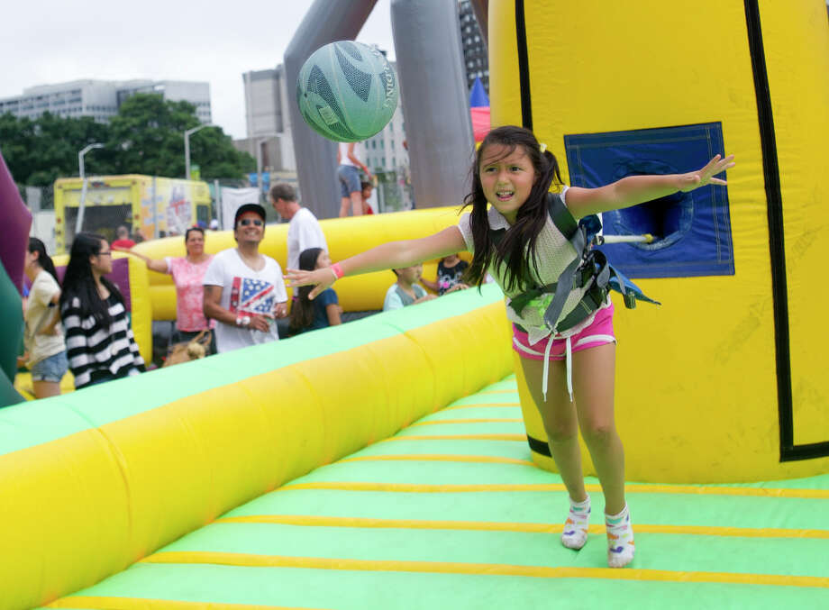 Allison Benavides, 5, plays on an inflatable during Pork in the Park at Mill River Park on Saturday, July 13, 2013. Photo: Lindsay Perry / Stamford Advocate
