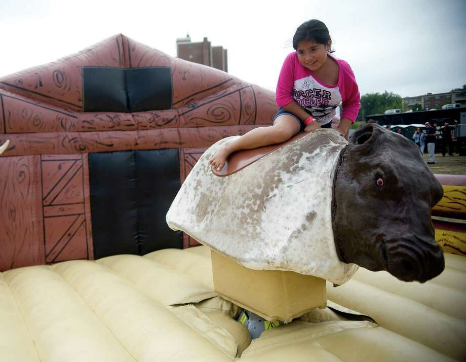 Jennifer Lumes, 9, rides the mechanical bull during Pork in the Park at Mill River Park on Saturday, July 13, 2013. Photo: Lindsay Perry / Stamford Advocate