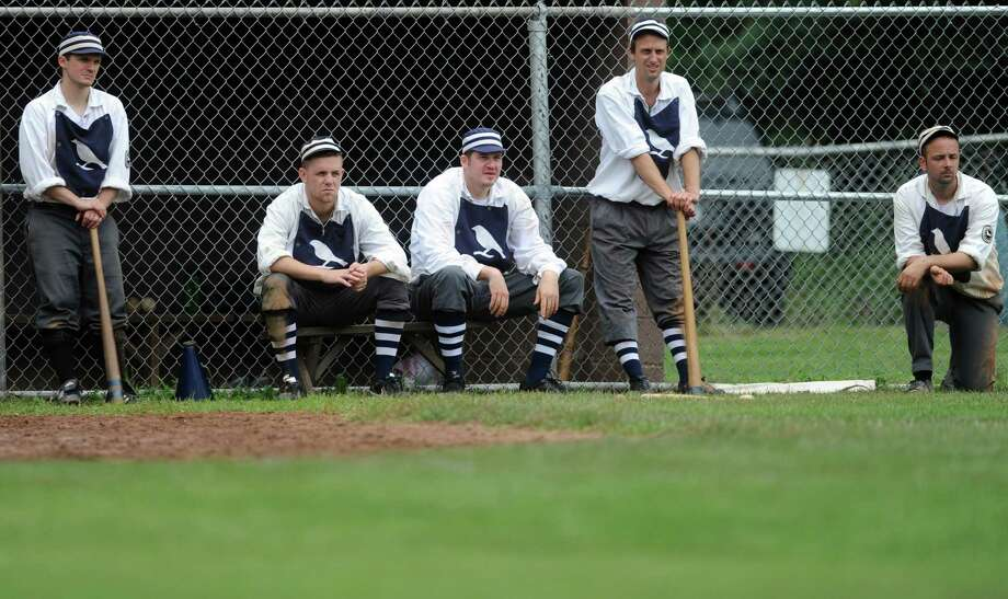 Players on Billy Barney's Blue Boys team watch game action against the Nutmegs during an exhibition game with 1860's rules on the field at VeteranâÄôs Park in Easton, Conn. Saturday, July 13, 2013.  Both teams are part of the Coltsville Vintage Baseball League. Photo: Autumn Driscoll / Connecticut Post