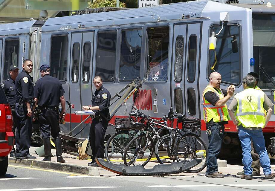 Investigators survey the damage to the Muni light rail train after the crash on Third Street. Photo: Michael Macor, San Francisco Chronicle