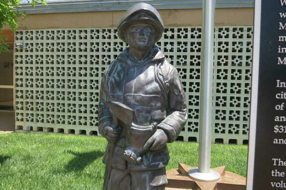 A statue outside the Sunray City Hall commemorates the volunteer firefighters who died while battling a 1956 oil refinery fire near the small Panhandle town.