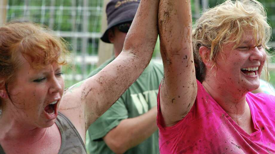 "Liz Beller, left, the chairwoman of the Wakeman Town Farm board of directors, congratulates Patti Popp, of Sport Hill Farm in Easton, for her victory in the farm gal mud ""wrestling"" event Saturday at the farm. Photo: Jarret Liotta / Westport News contributed"