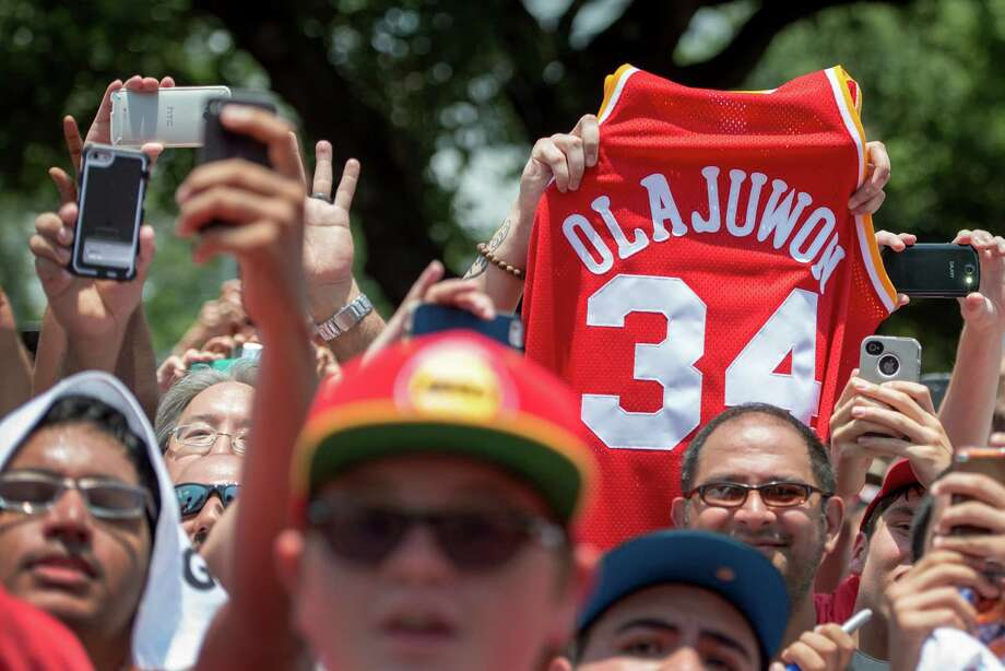 Fans hold up the jersey of Houston Rockets legend Hakeem Olajuwon as Dwight Howard is introduced as the newest member of the team during a rally outside Toyota Center on Saturday, July 13, 2013, in Houston. The free agent officially joined the Rockets on Saturday with a news conference and public rally. ( Smiley N. Pool / Houston Chronicle ) Photo: Smiley N. Pool, Staff / © 2013  Houston Chronicle