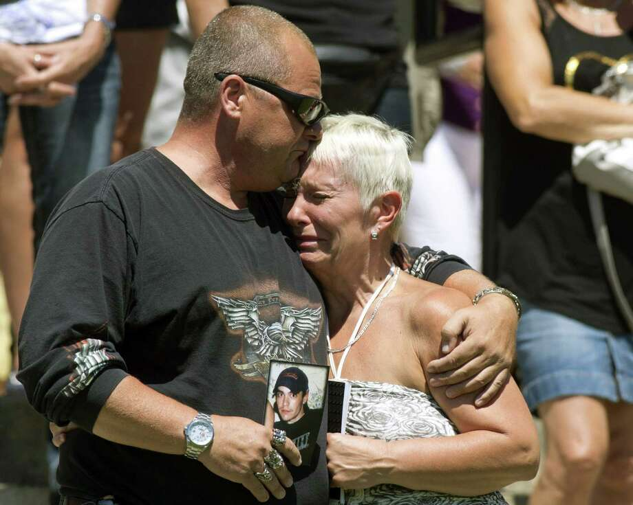 Lise Doyon is comforted by Jeannot Labrecque as church bells chime 50 times for the victims of a derailed oil train. Photo: Jacques Boissinot / Canadian Press