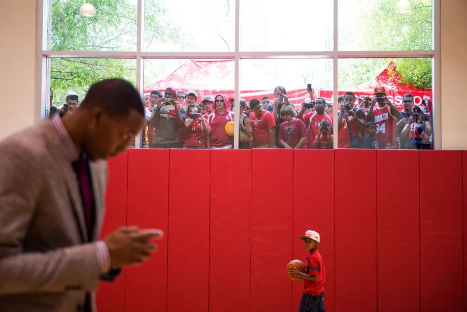 Fans crowd against windows for a peek at Dwight Howard as sends a text while he waiting for a photo shoot after he was introduced as the newest member of the Houston Rockets. Photo: Smiley N. Pool, Houston Chronicle