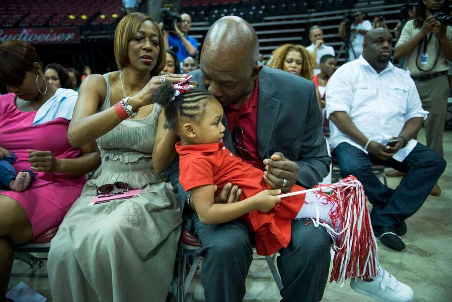 Dwight Howard's parents Sheryl and Dwight play with his daughter Layla, 3, as their son is introduced at a press conference. Photo: Smiley N. Pool, Houston Chronicle