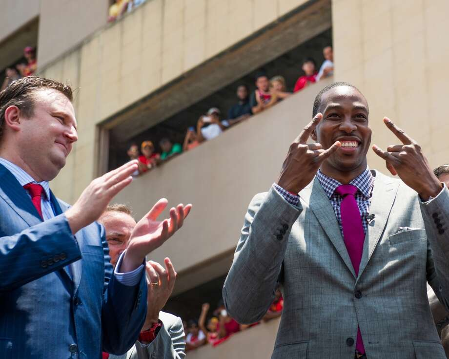 Dwight Howard, left, acknowledges the cheers of the the crowd, and general manager Daryl Morey. Photo: Smiley N. Pool, Houston Chronicle