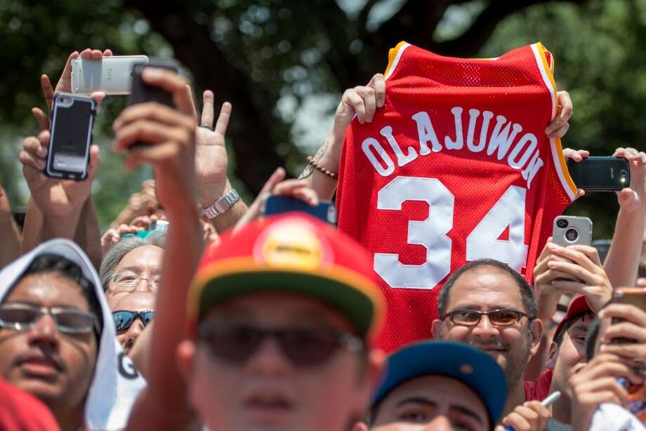 Fans hold up the jersey of Houston Rockets legend Hakeem Olajuwon as Dwight Howard is introduced. Photo: Smiley N. Pool, Houston Chronicle