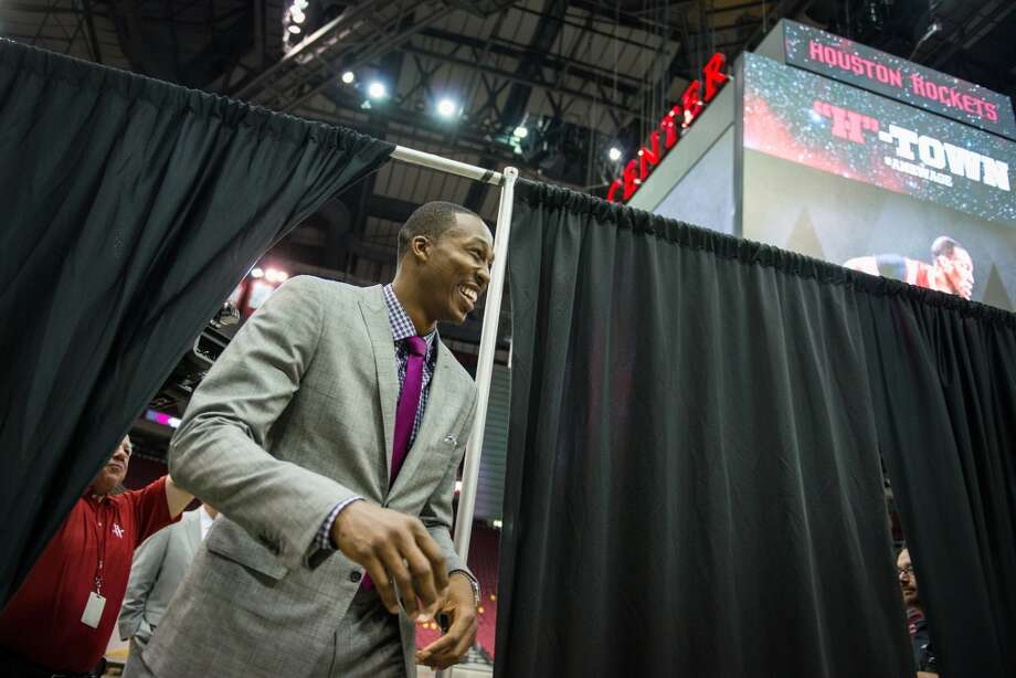 Dwight Howard smiles while emerging from behind a curtain as is introduced as the newest member of the Houston Rockets. Photo: Smiley N. Pool, Houston Chronicle