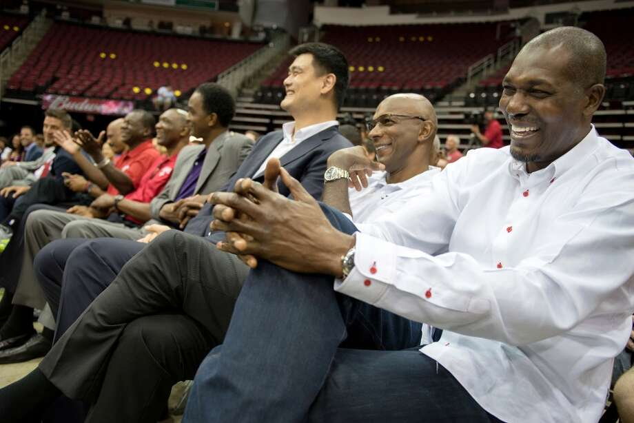 Hakeem Olajuwon, right, laughs with Clyde Drexler, Yao Ming and a row of other Houston Rockets legends. Photo: Smiley N. Pool, Houston Chronicle