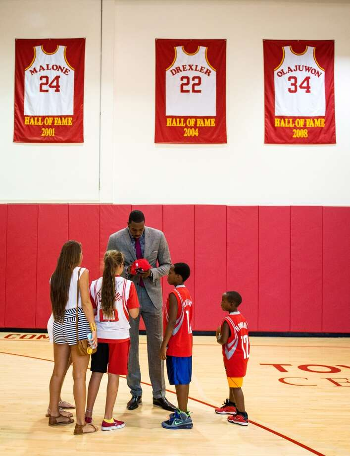 Dwight Howard signs autographs for a group of youngsters beneath banners on the practice court for the retired jerseys of Moses Malone, Clyde Drexler and Hakeem Olajuwon. Photo: Smiley N. Pool, Houston Chronicle