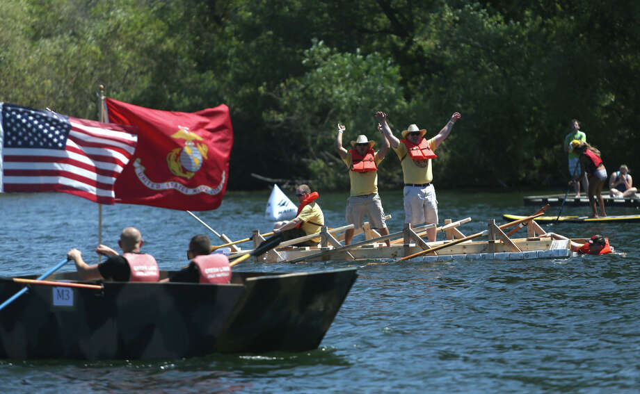 National Guard members celebrate after winning the military division during the annual Seafair Milk Carton Derby on Saturday, July 13, 2013 at Green Lake in Seattle. People lined the shores of the lake to watch teams compete in vessels made buoyant by empty milk cartons. The event is a Seattle summer tradition. Photo: JOSHUA TRUJILLO, SEATTLEPI.COM
