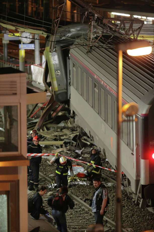 Rescuers work at the scene where a train derailed at a station in Bretigny sur Orge, south of Paris, Saturday, July 13, 2013. A packed passenger train skidded off its rails after leaving Paris on Friday, leaving seven people believed dead and dozens injured as train cars slammed into each other and overturned, authorities said. (AP Photo/Michel Euler) ORG XMIT: MEU114 Photo: Michel Euler / AP