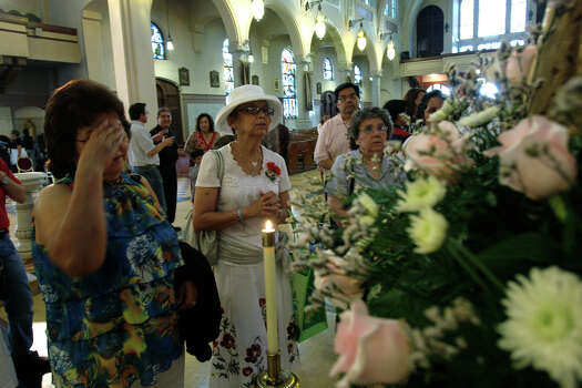 People gather around a icon of Our Lady of Mount Carmel after a Mother's Day Mass at the Basilica of the National Shrine of the Little Flower, Sunday, May 10, 2009. Photo: JERRY LARA, San Antonio Express-News / glara@express-news.net