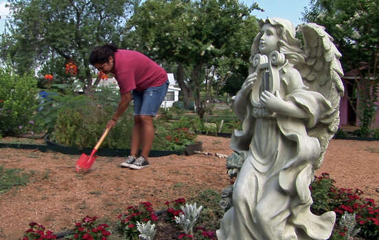 Volunteer Nadia Gomez works on clearing a path in a garden belonging to the Basilica of the Little Flower National Shrine on July 31, 2008. Though much of the work to maintain the garden is done by volunteers like Gomez, the shrine gets a supplement from selling salsa that is made from the tomatoes grown in the garden. Photo: KIN MAN HUI, San Antonio Express-News / SAN ANTONIO EXPRESS-NEWS