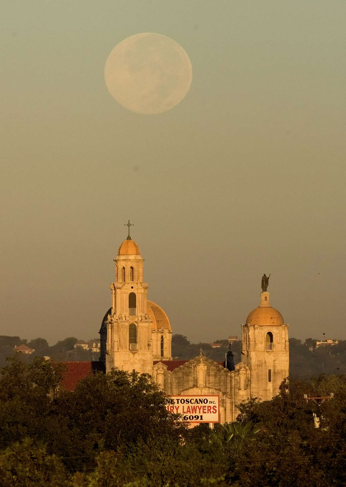 The full moon sets Friday morning Oct. 26, 2007 behind the Basilica of the National Shrine of the Little Flower.