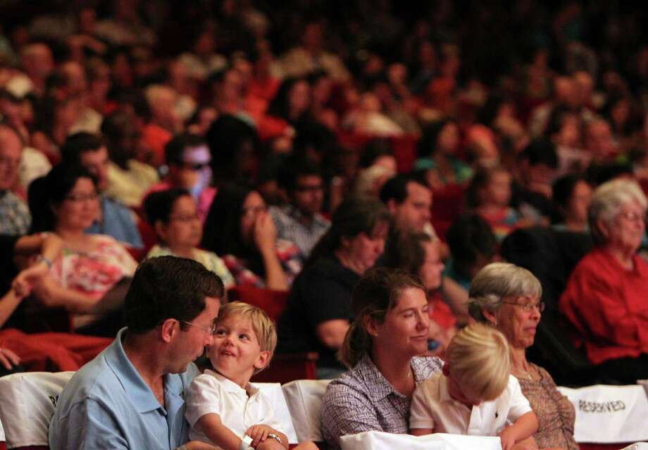 A family enjoys the narration of Milo Hamilton as the symphony plays 'Take Me Out to the Ball Game' on the main stage during 'Day of Music' at Jones Hall on Saturday, July 13, 2013, in Houston. Photo: Mayra Beltran / © 2013 Houston Chronicle